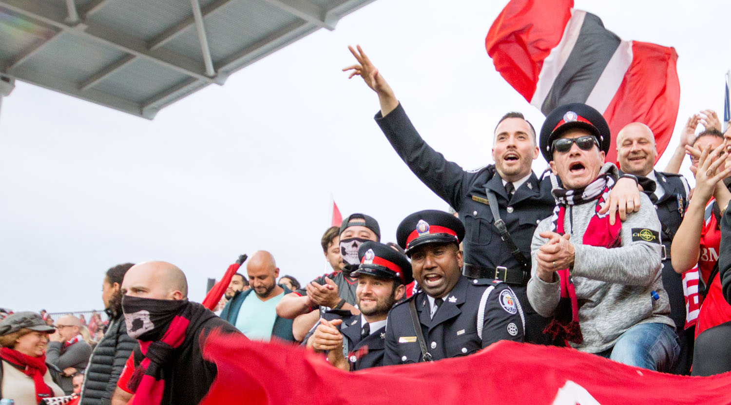 The Toronto Police Service celebrates with Toronto FC fans at BMO Field in Toronto Canada. Image by Dennis Marciniak of denMAR Media.