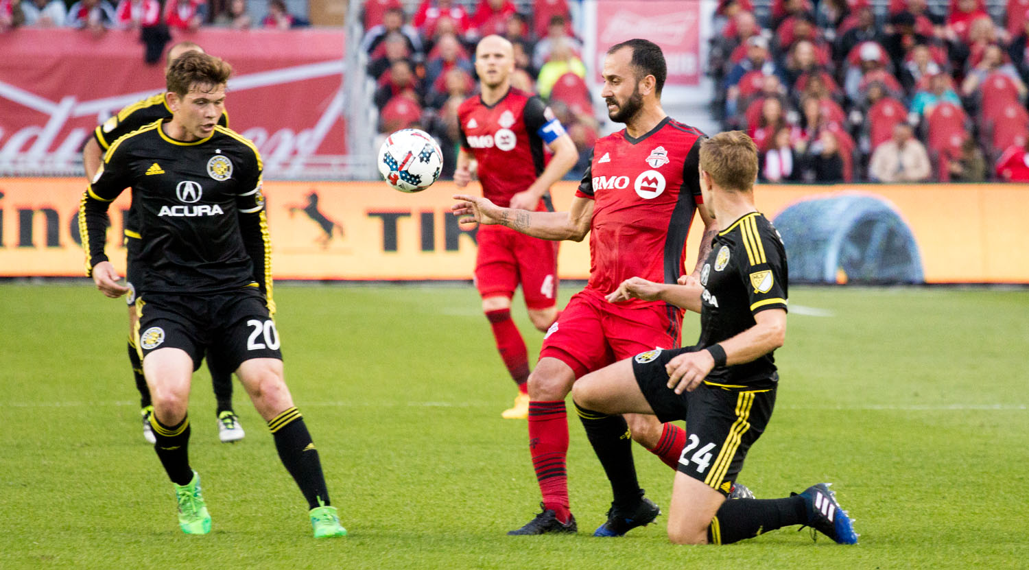 Toronto FC and Columbus Crew SC players attempt to deal with an aerial ball. Image by Dennis Marciniak of denMAR Media.