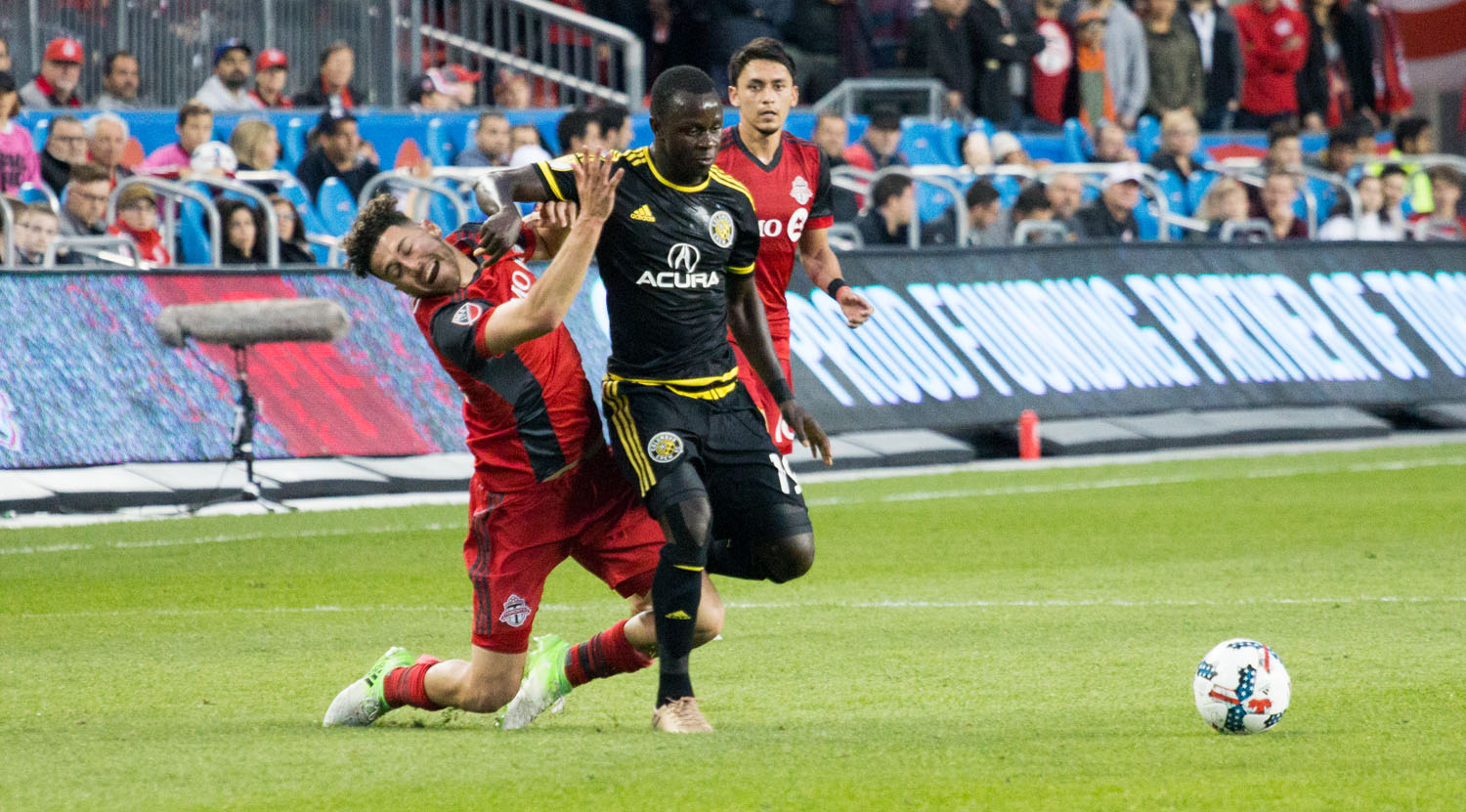 Jonathan Osorio gets a nice slap in the face from Kekuta Manneh. Image by Dennis Marciniak of denMAR Media.