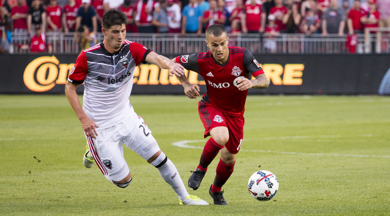 Sebastian Giovinco trying to get away from a DC United player. Image by Dennis Marciniak of denMAR Media.
