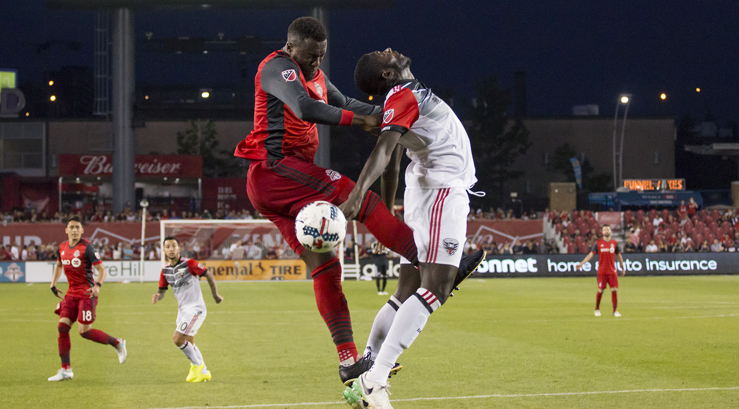 Jozy Altidore goes for the ball but ends up almost kicking a DC United player in a bad place. Image by Dennis Marciniak of denMAR Media.