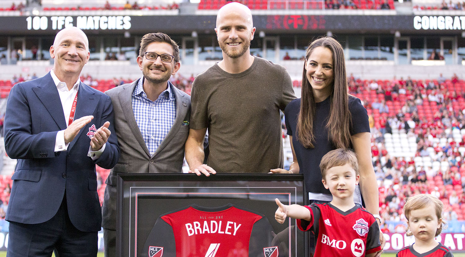 Bill Manning , Tim Bezbatchenko, Michael Bradley, and his wife Amanda Barletta pose with a commemorative jersey for Michael Bradley's 100th match with Toronto FC. Image by Dennis Marciniak of denMAR Media.