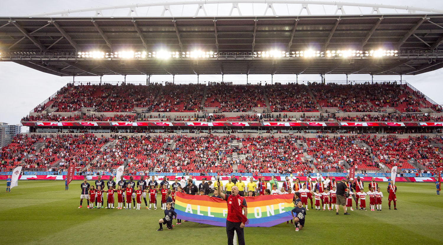The national anthem at BMO Field with Pride ceremonies taking place two nights ahead of the Pride Parade in Toronto, Canada. Image by Dennis Marciniak of denMAR Media.