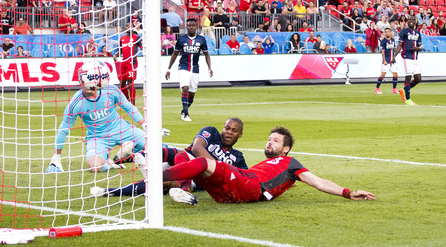 Drew Moor gets a ball across the box from Tsubasa Endoh and slides it past New England goalkeeper Cody Cropper to make it 1-0 in the first half of tonight's Toronto FC game. Image by Dennis Marciniak of denMAR
