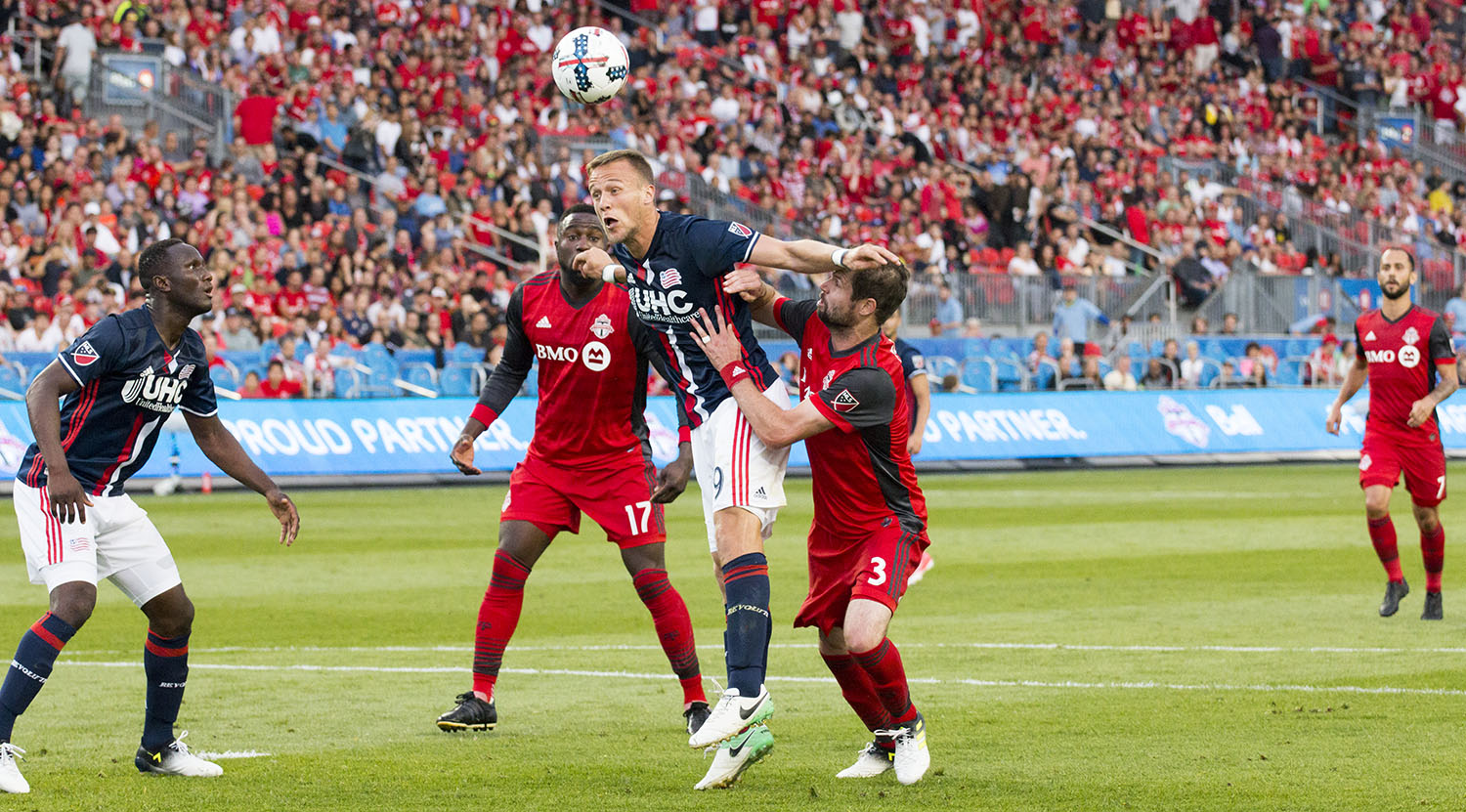 A New England Revolution player heads the ball away from the net at BMO Field. Image by Dennis Marciniak of denMAR