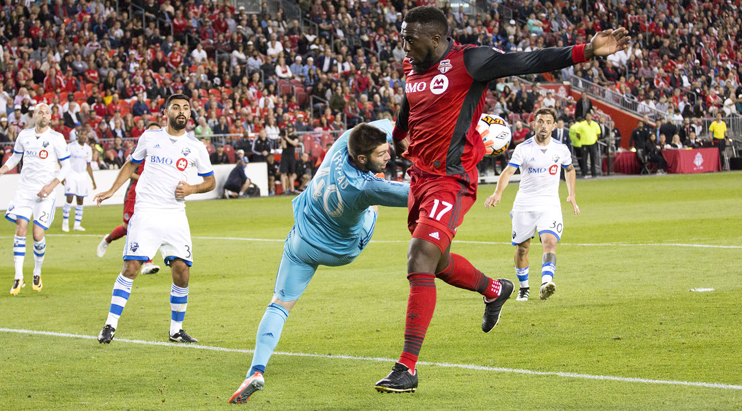 Jozy Altidore tries to get the ball past the Montreal Impact goalkeeper as he snatches it out of the air with his hands.Image by Dennis Marciniak of denMAR Media.
