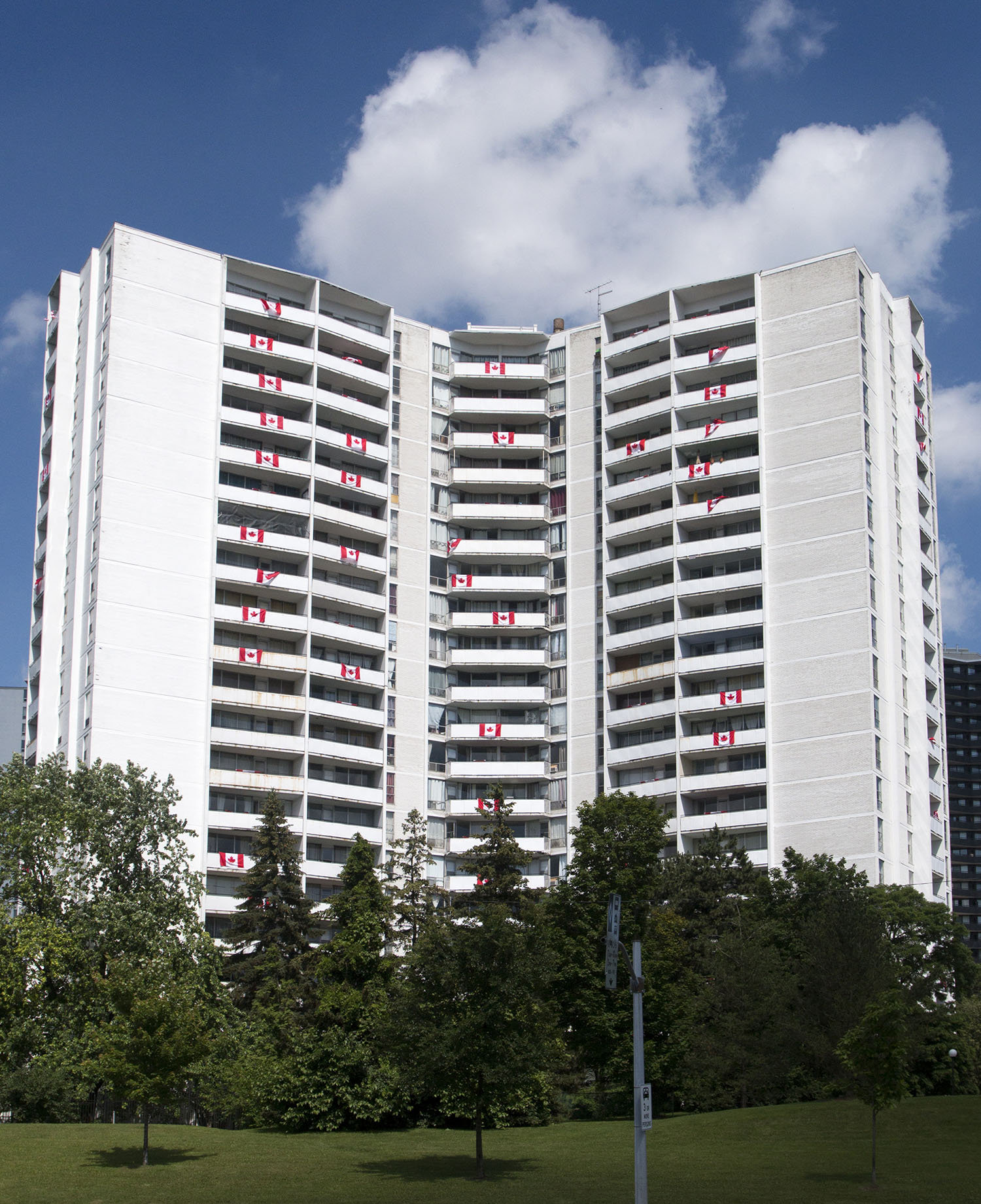 Canadian flags hang from balconies in Toronto, Ontario for the Canada Day 150 celebrations in 2017. The building is on Gradyon Hall Drive and Don Mills near the 401. Image by Dennis Marciniak of denMAR Media.