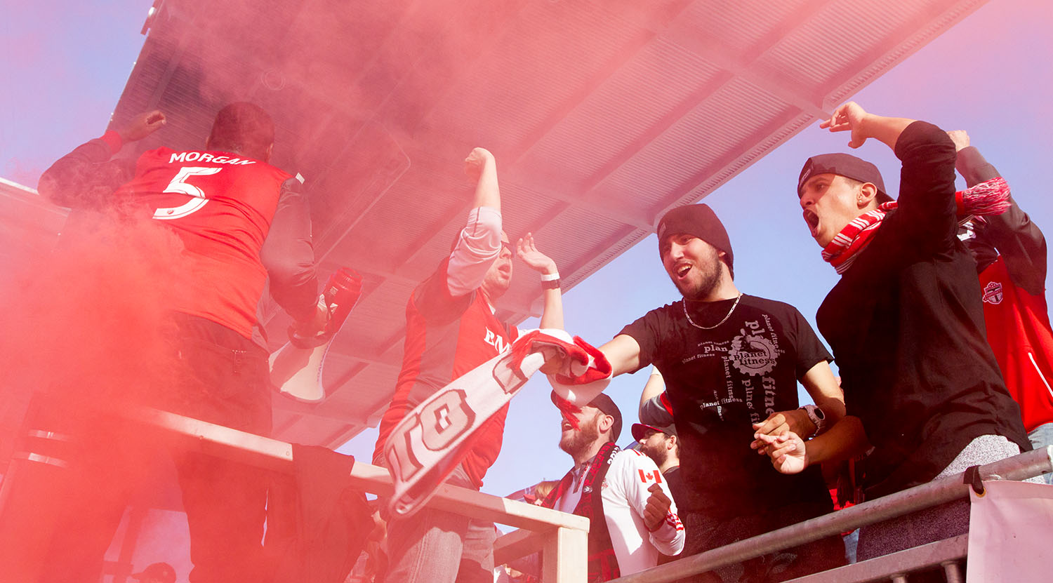 South End supporters celebrate amidst the red smoke after the first goal on the day. Image by Dennis Marciniak.