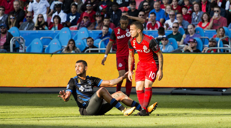 Sebastian Giovinco and a San Jose Earthquakes player clash in a shaft of light during a regular season MLS match. Image by Dennis Marciniak of denMAR Media.