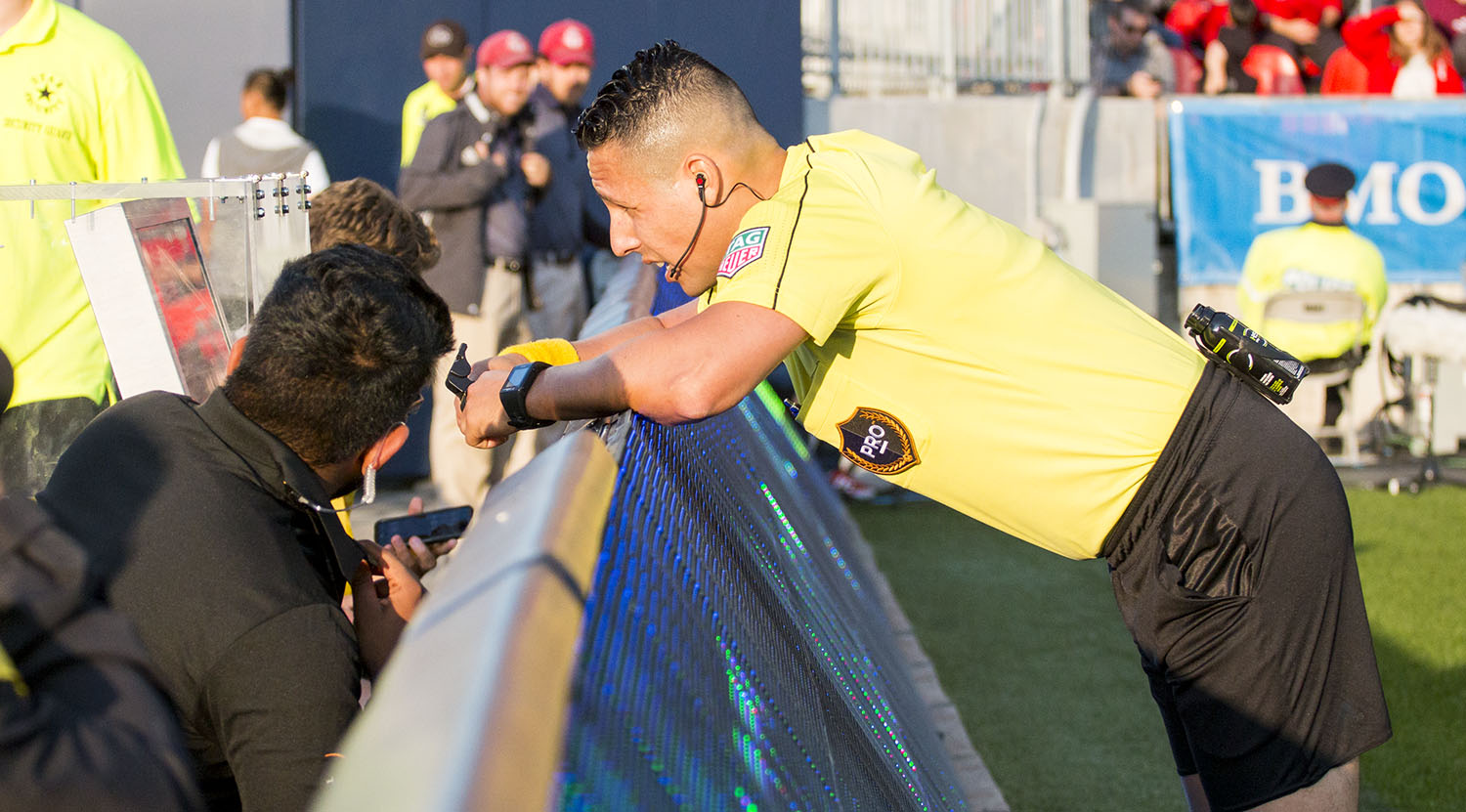 Referee Jose Carlos Rivero check the call by Video Assistant Referee Yusri Rudolf that would result in a red card during the first Video Review at BMO Field. Image by Dennis Marciniak of denMAR Media.