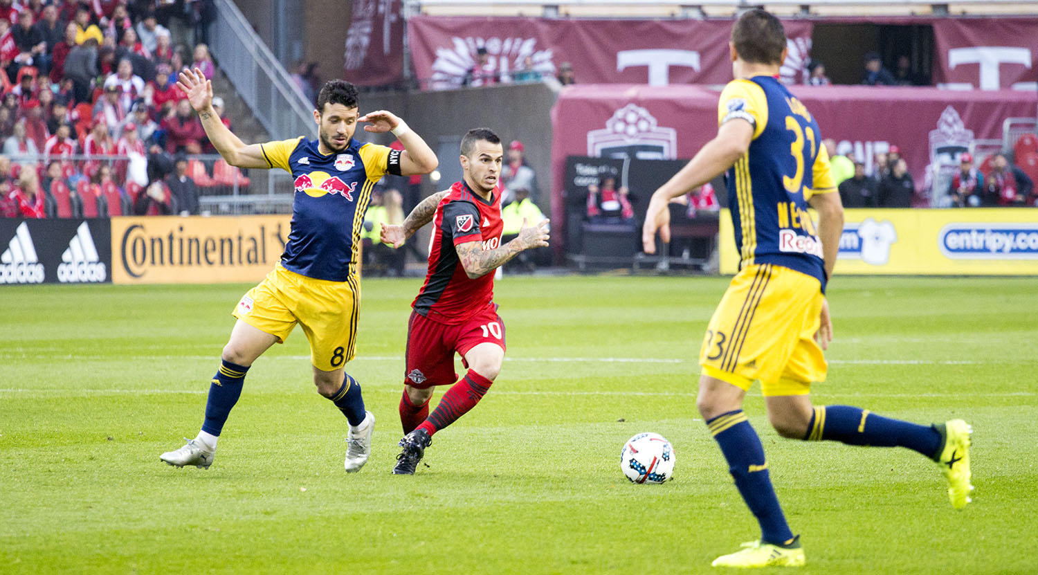 Sebastian Giovinco tries to get the ball past two NYRB defenders during a 2017 MLS playoff game. Image by Dennis Marciniak of denMAR Media.