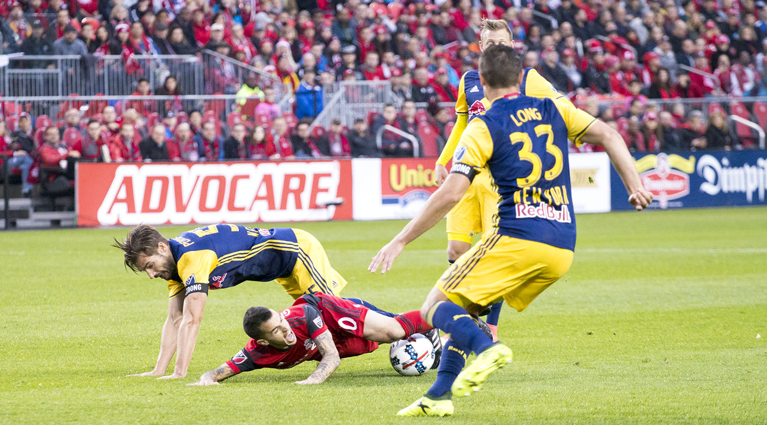 Sebastian Giovinco is taken down to ground as he attempts to get to the ball surrounded by three NYRB players. Image by Dennis Marciniak of denMAR Media.