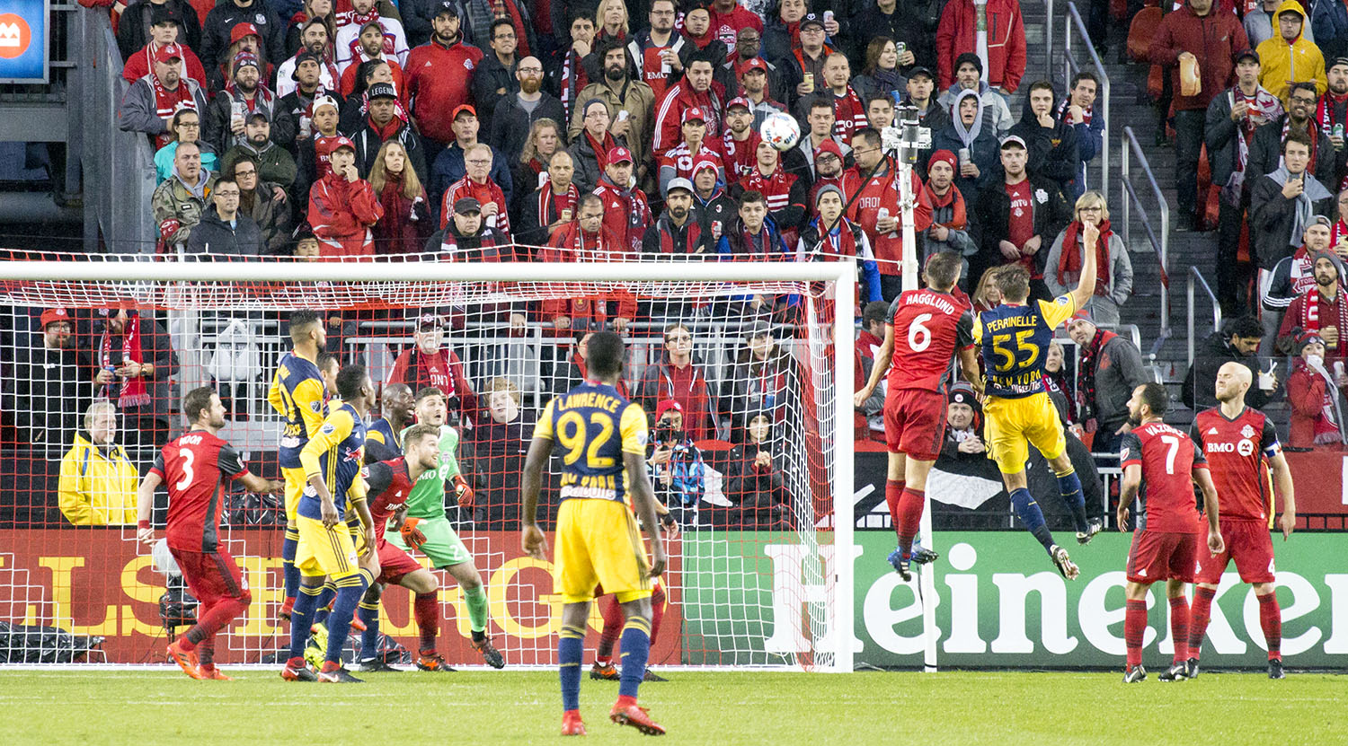 Players go up into the air for a ball in front of the south end at BMO Field. Image by Dennis Marciniak of denMAR Media.