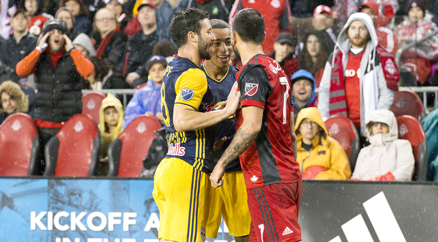 Two NYRB players argue with Víctor Vázquez Solsona during a playoff match in 2017 at BMO Field. Image by Dennis Marciniak of denMAR Media.