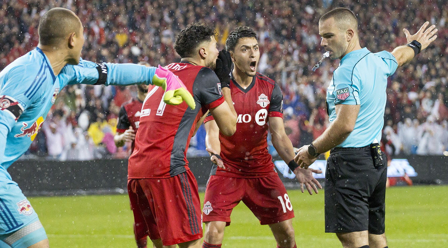 Luis Robles and Marky Delgado argue with the first official Chris Penso as to whether the ball went past the goal line or not. Image by Dennis Marciniak of denMAR Media.
