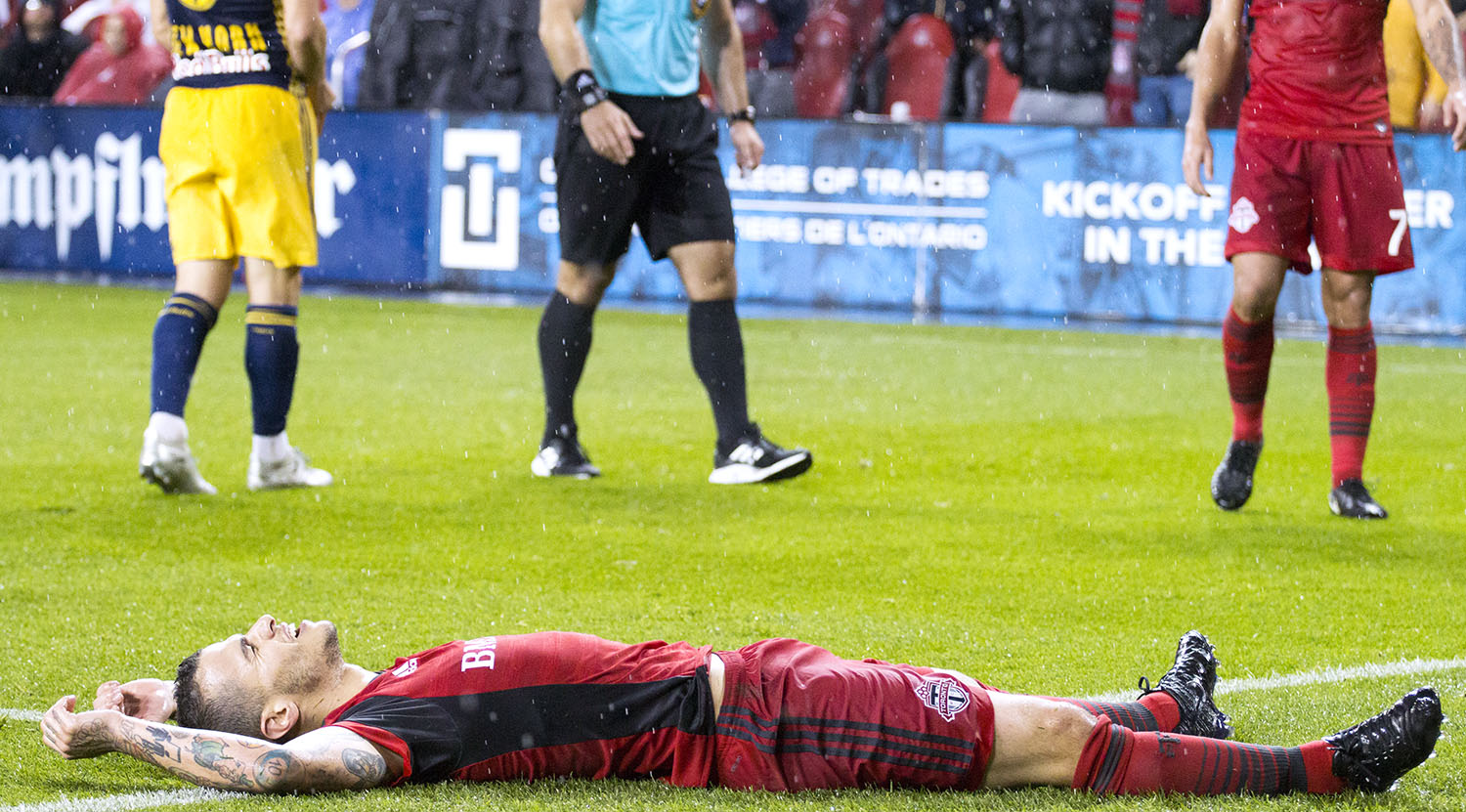 Sebastian Giovinco goes to ground and has a relax as the pouring rain comes down on him during a playoff match in 2017. Image by Dennis Marciniak of denMAR Media.