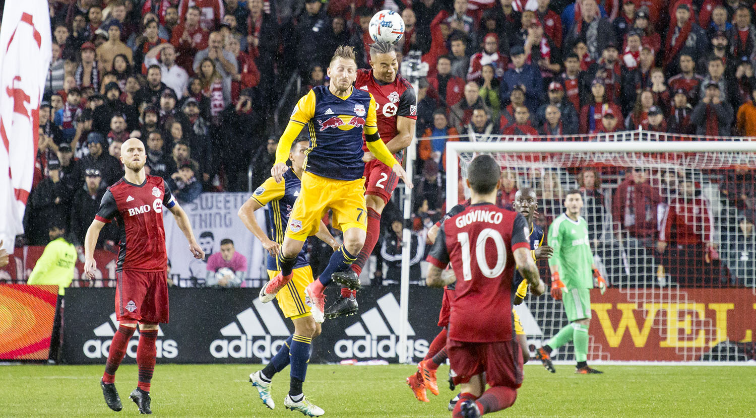 A NYRB and Toronto FC player go into the air for a header during a rainy match in 2017. Image by Dennis Marciniak of denMAR Media.