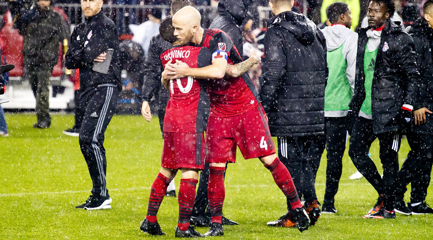 Sebastian Giovino and Michael Bradley give each other a hug in the rain after advancing 2-2 on away goals to the next round of the MLS playoffs.