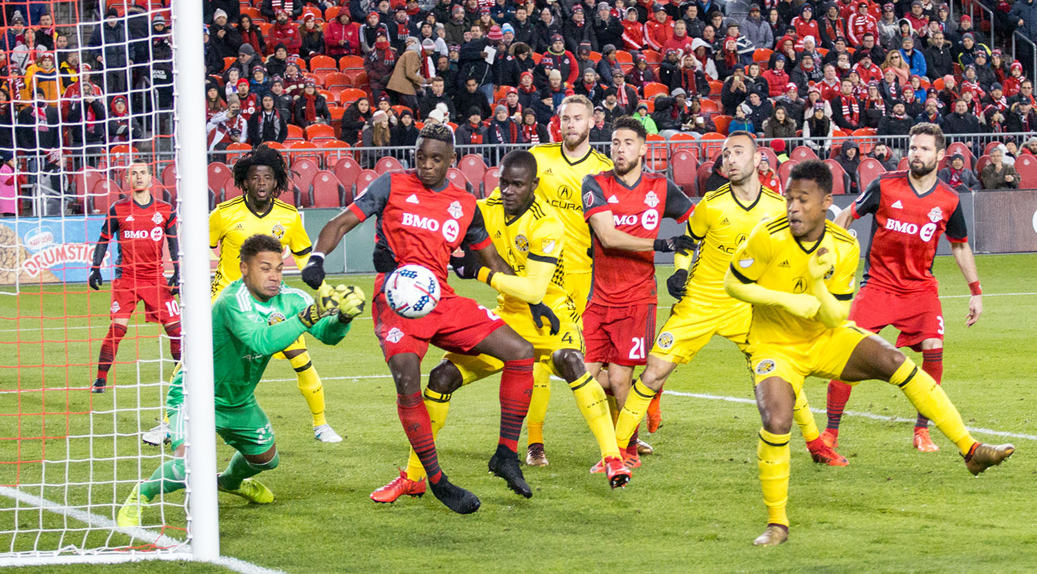 Columbus Crew goalkeeper Zack Steffen punches the ball away from danger as both Toronto FC and Columbus Crew crowd the 18 yard box.Image by Dennis Marciniak of denMAR Media.
