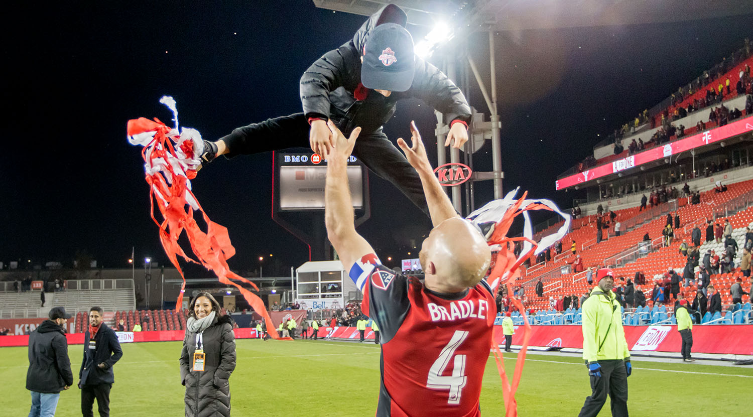 Michael Bradley throwing his son into the air as streamers thrown during the match stick to his feet in celebration of the 2017 Eastern Confernce Final win in 2017. Image by Dennis Marciniak of denMAR Media.