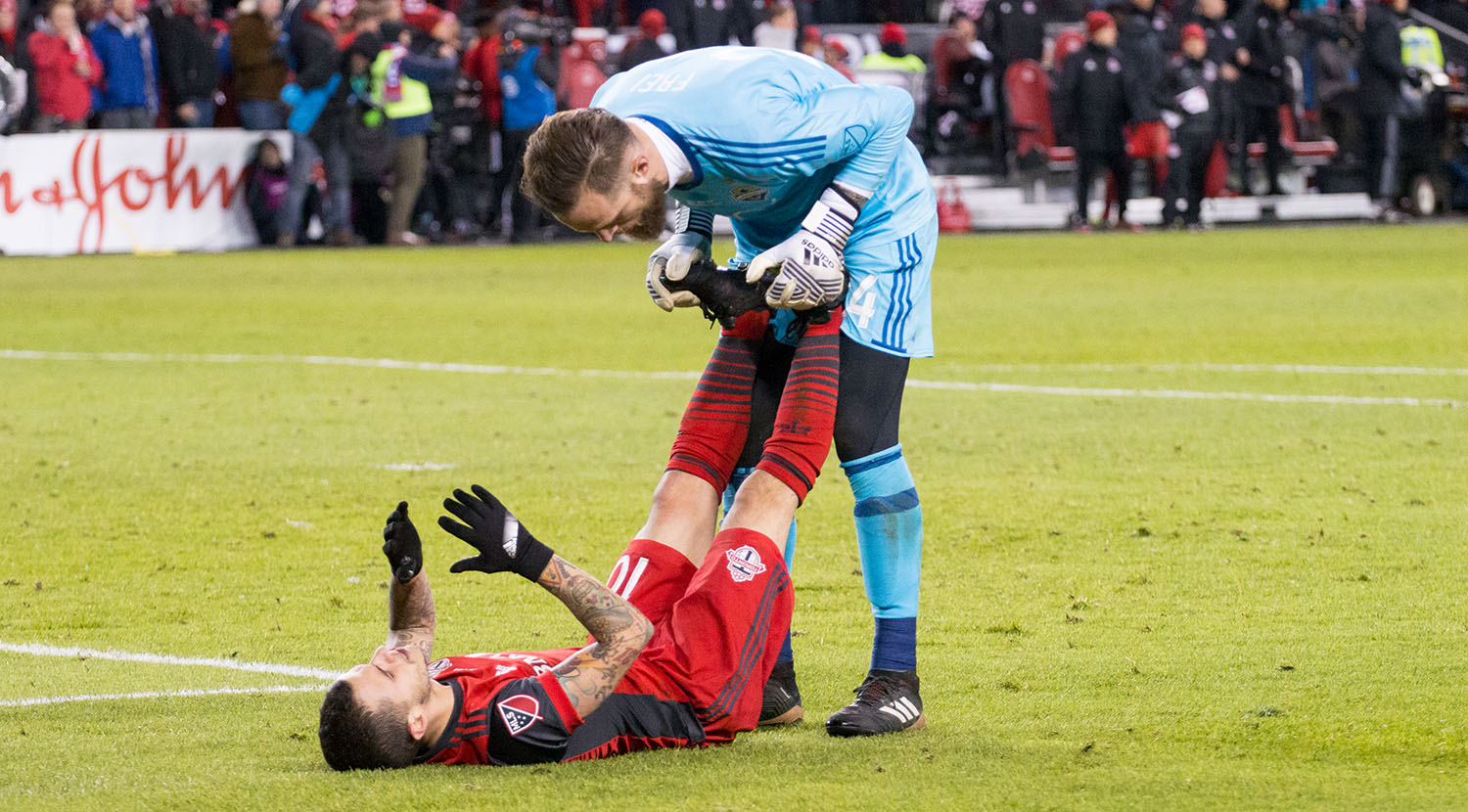 Stefan Frei helps out Sebastian Giovinco after cramping up on the ground in the attacking 18 yard box.Image by Dennis Marciniak of denMAR Media.