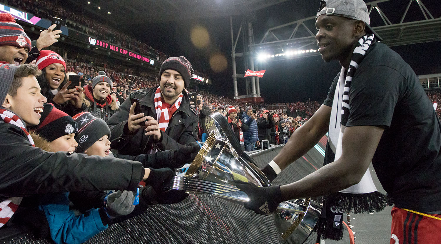 Chris Mavinga lets some young supporters touch the MLS cup as he brings the trophy the east end.Image by Dennis Marciniak of denMAR Media.