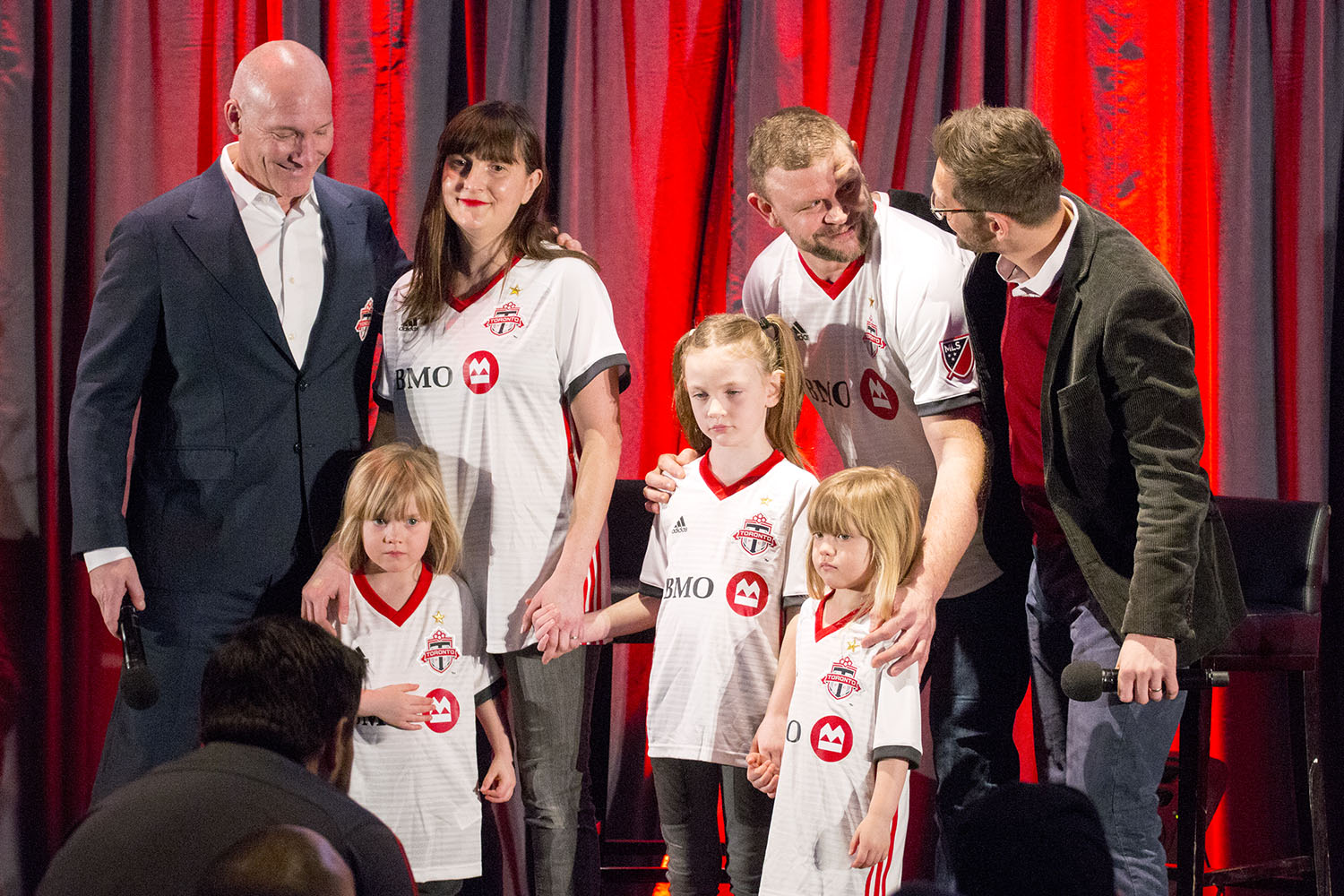 Tim Bezbatchenko and Bill Manning have a family of season ticket holders on the stage to model the new 2018 Toronto FC alternate jersey at Real Sports Bar and Grill in Toronto, Canada. Image by Dennis Marciniak of denMAR Media.