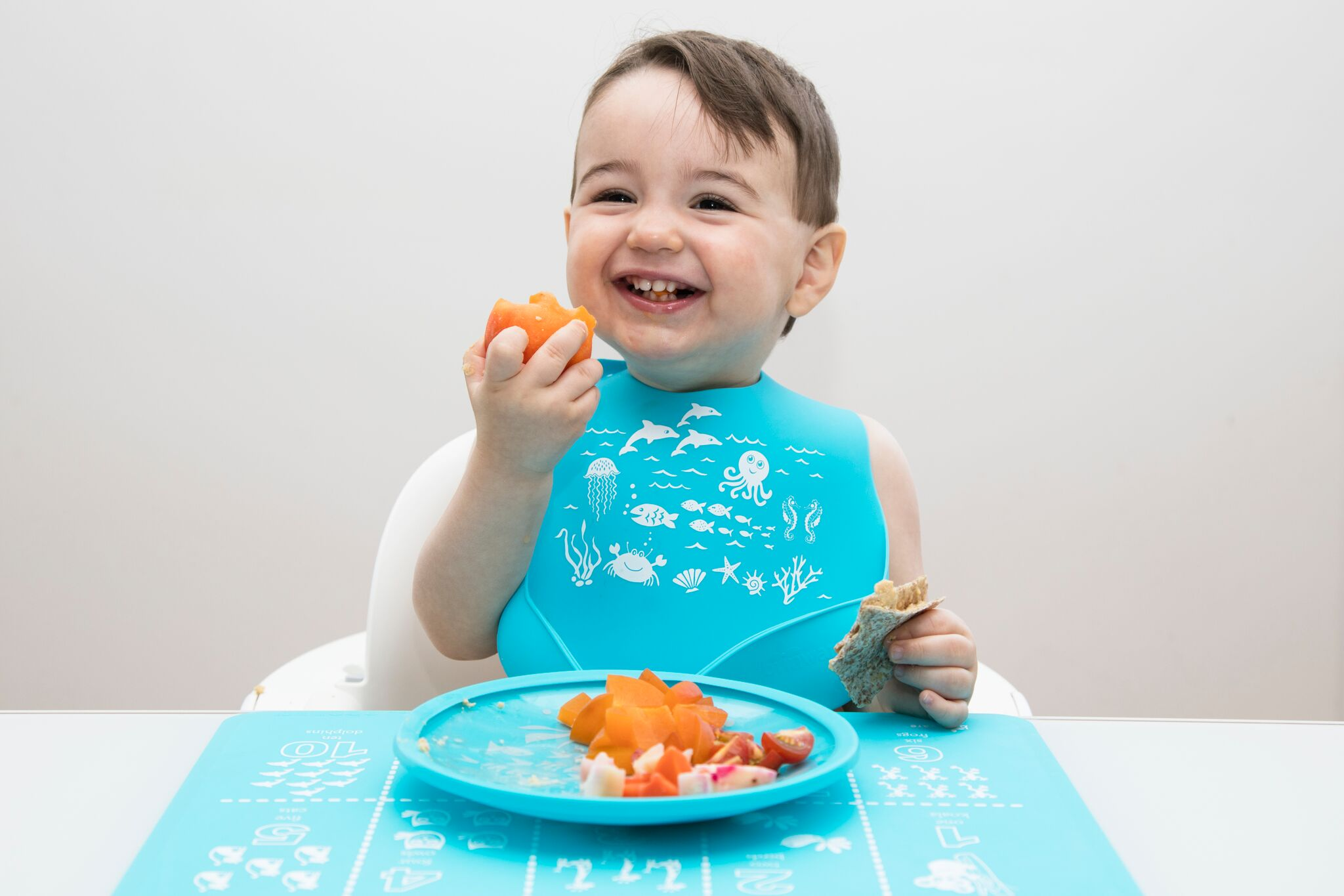 My son enjoying his lunch with  Brinware's bib, plate and mat .