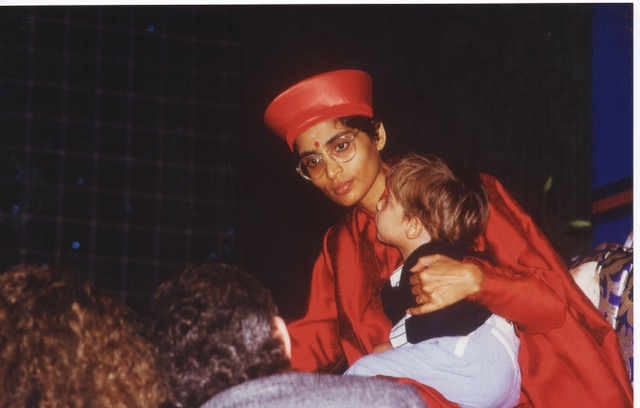 Sage as a little boy in Gurumayi's lap while she is blessing devotees