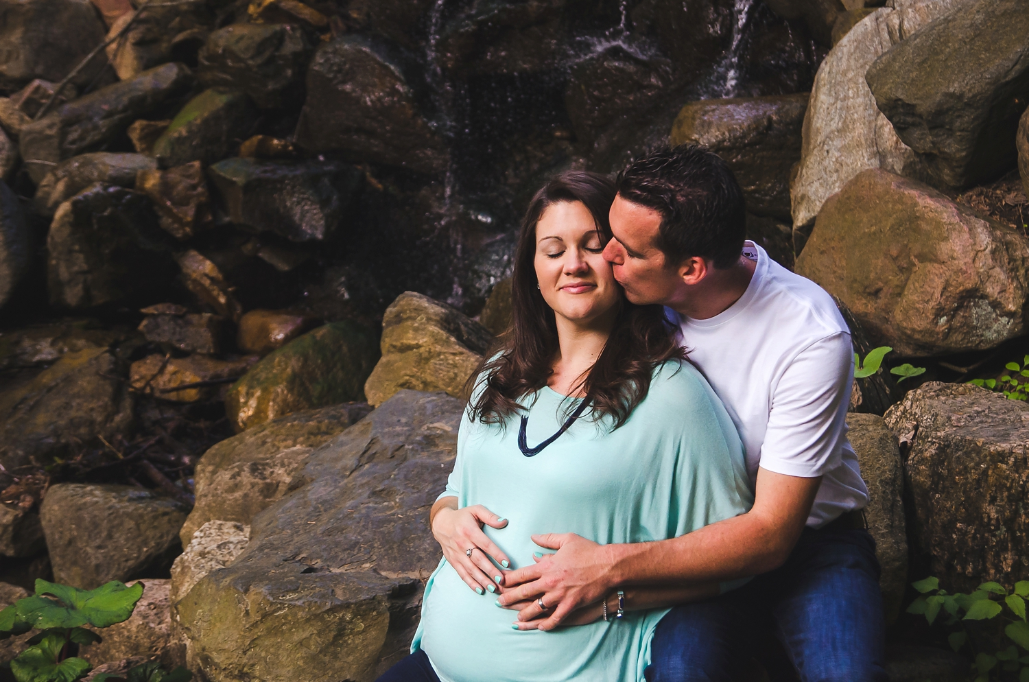 Mom and dad pose for maternity pictures by a waterfall.