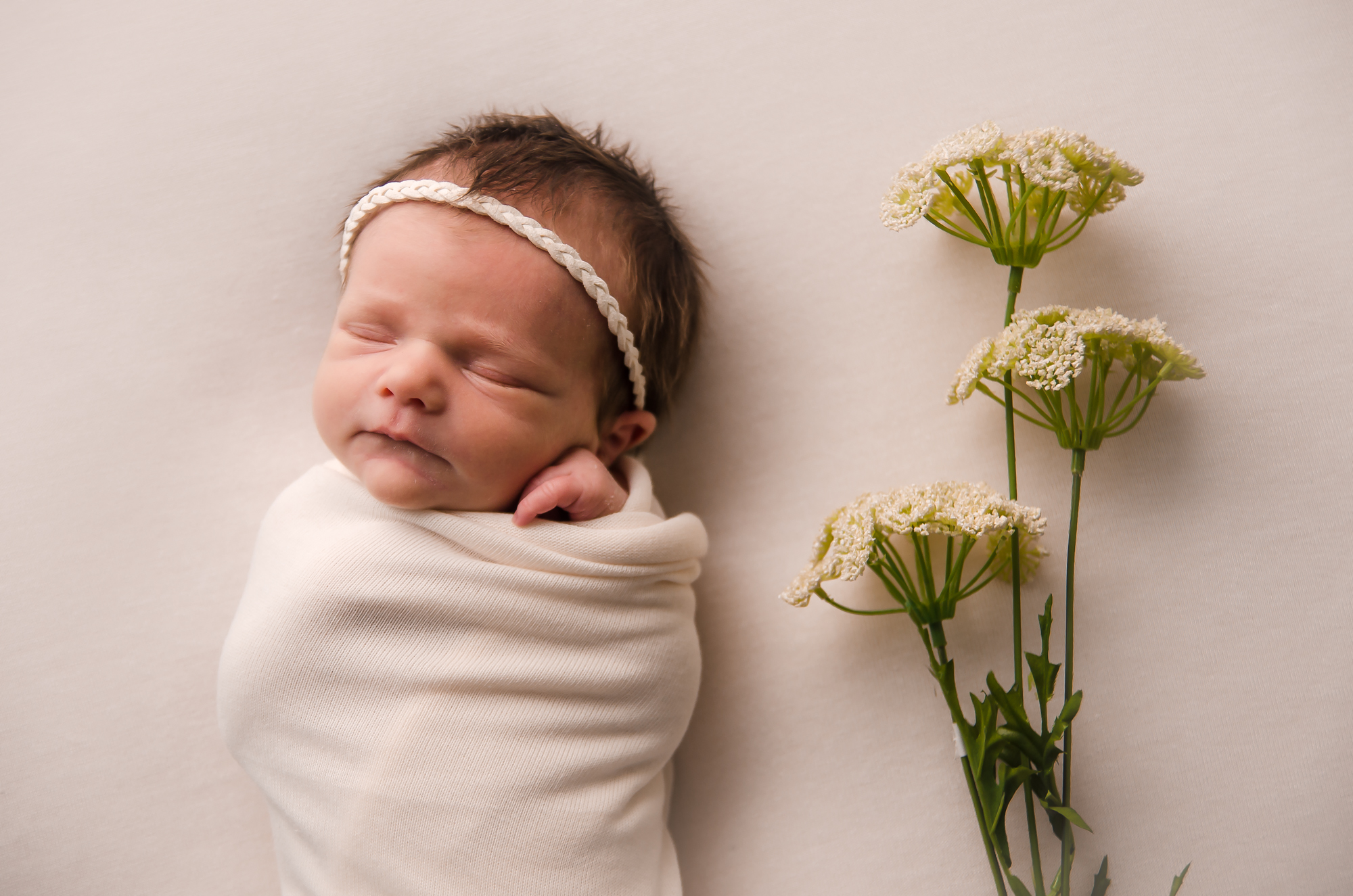Newborn girl is posed on a minimal backdrop with neutral colors