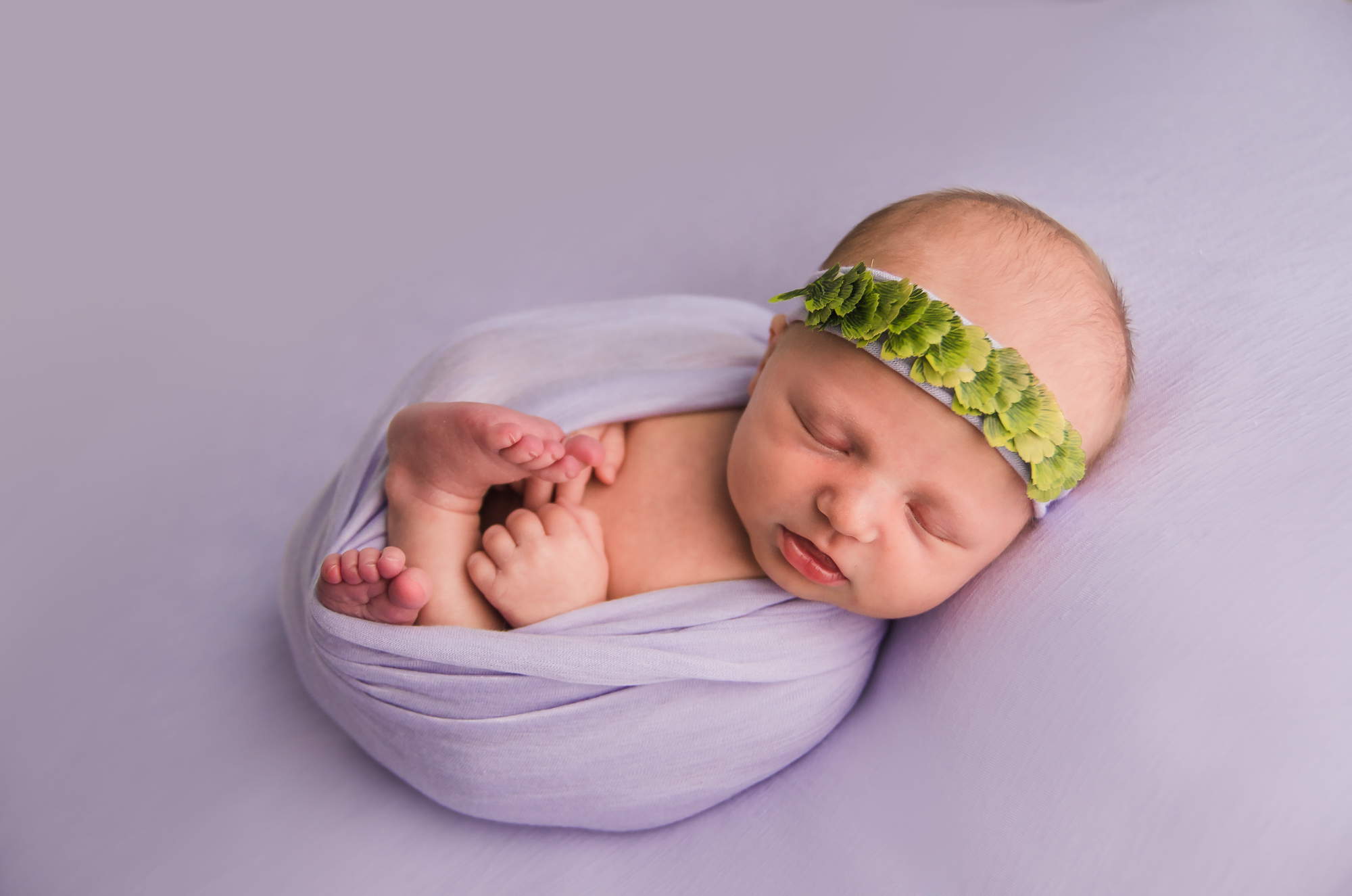 A newborn is posed on a beanbag with a purple wrap and tieback