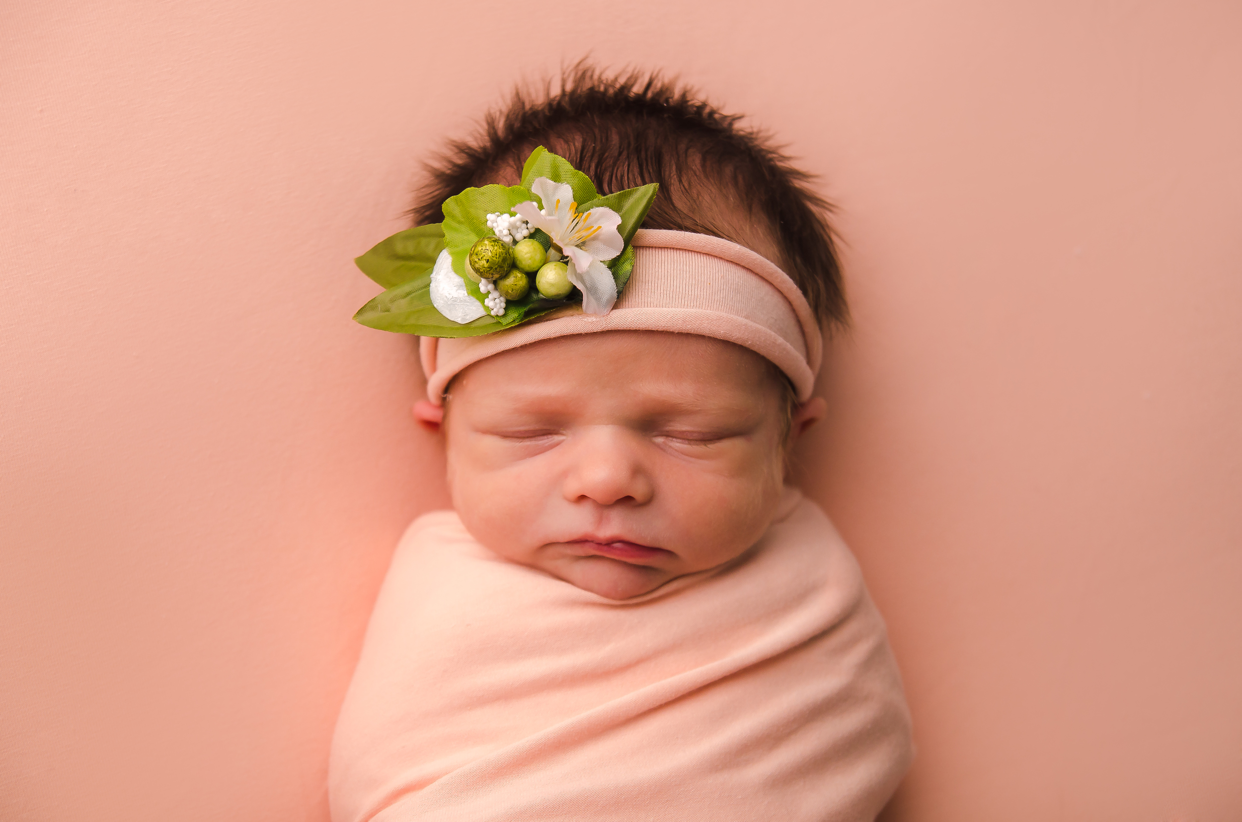 Newborn girl wears a tieback headband and is posed on a light pink blanet