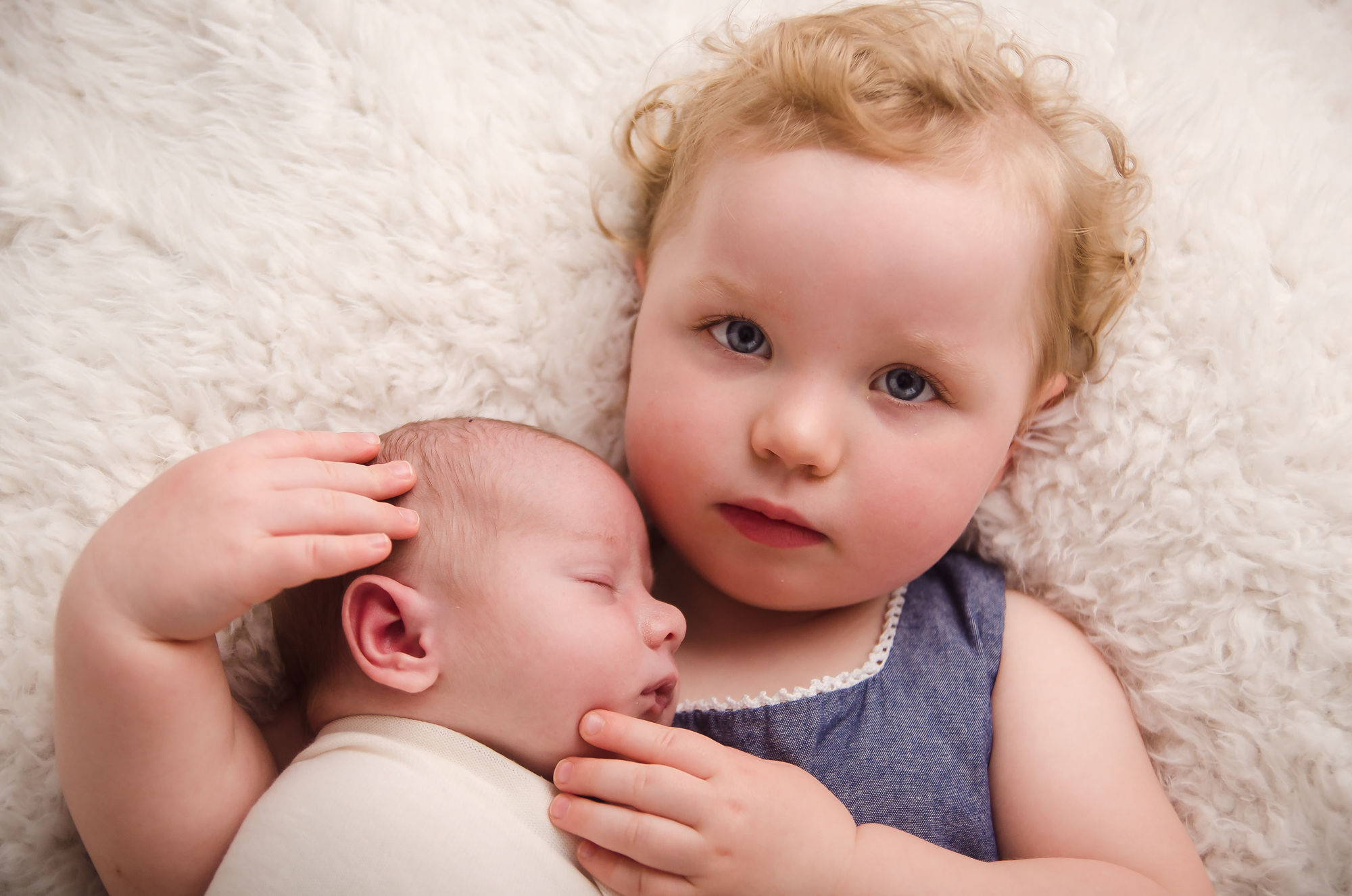 Big sister loving on her new brother during his newborn session in Indianapolis