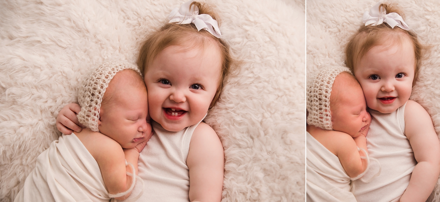 Big sister smiles while she holds her newborn sister