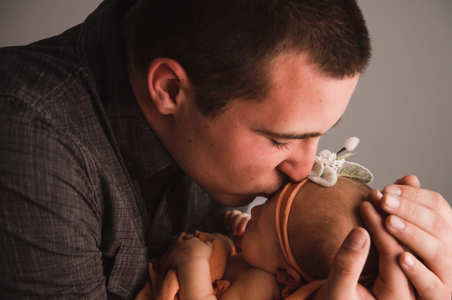 Dad gives his newborn daughter a kiss