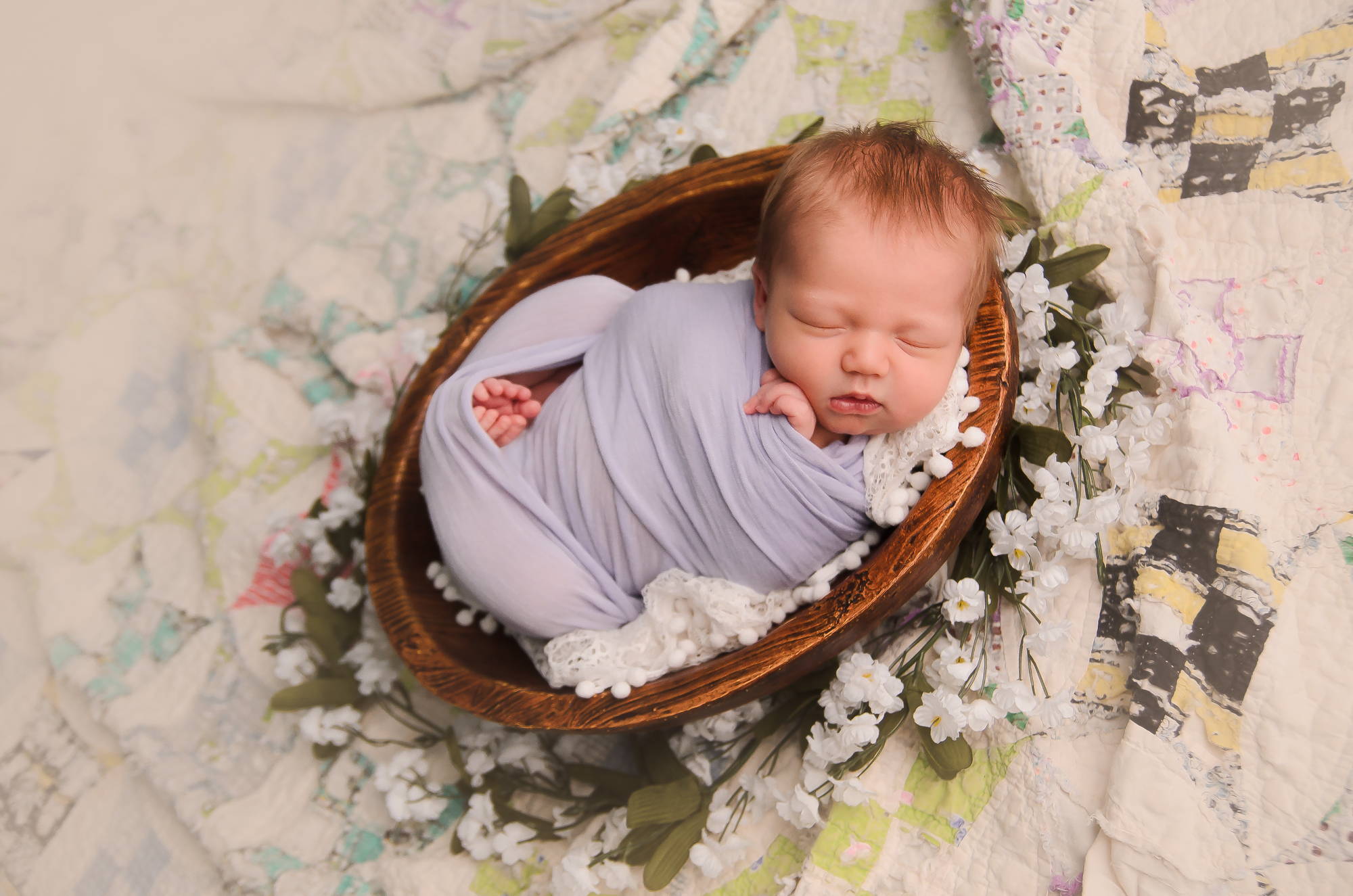 newborn girl posed on a vintage quilt in a wooden bowl