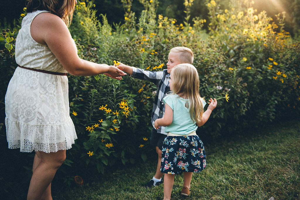 kids give wildflowers to their mom