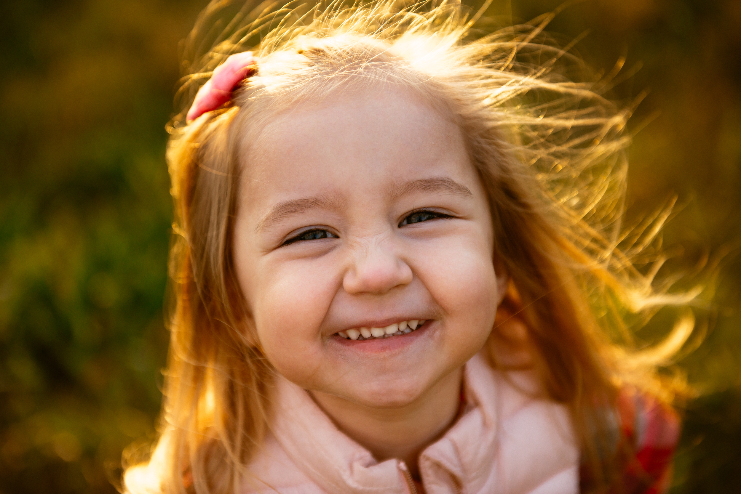 little girl smiles for the camera at a family session in indianapolis
