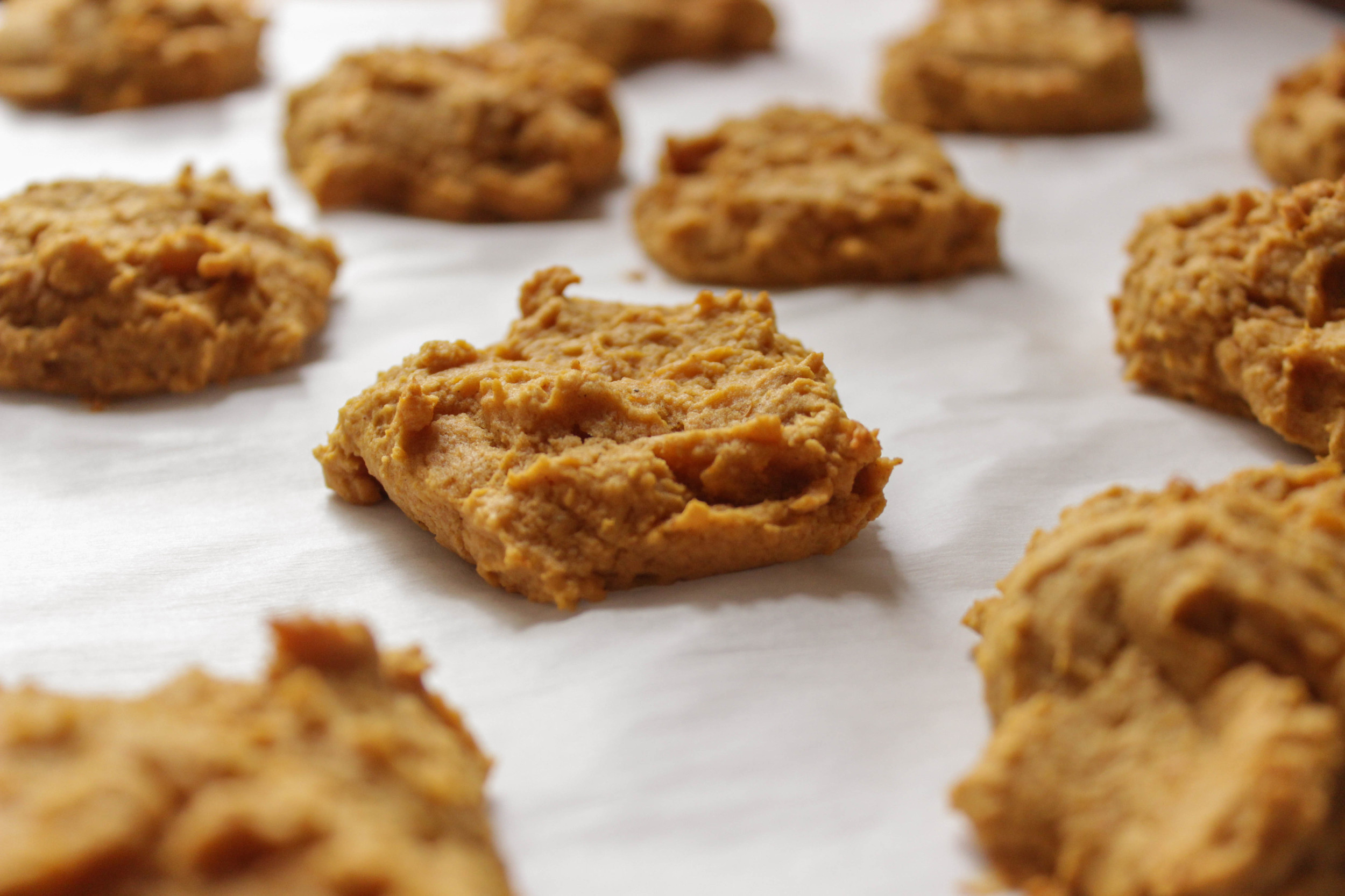 Bake the cookies for 12-15 minutes, until very lightly browned and the center springs back up when you poke it. Let them cool on the sheet for a few minutes before transferring them on the parchment to cooling racks.
