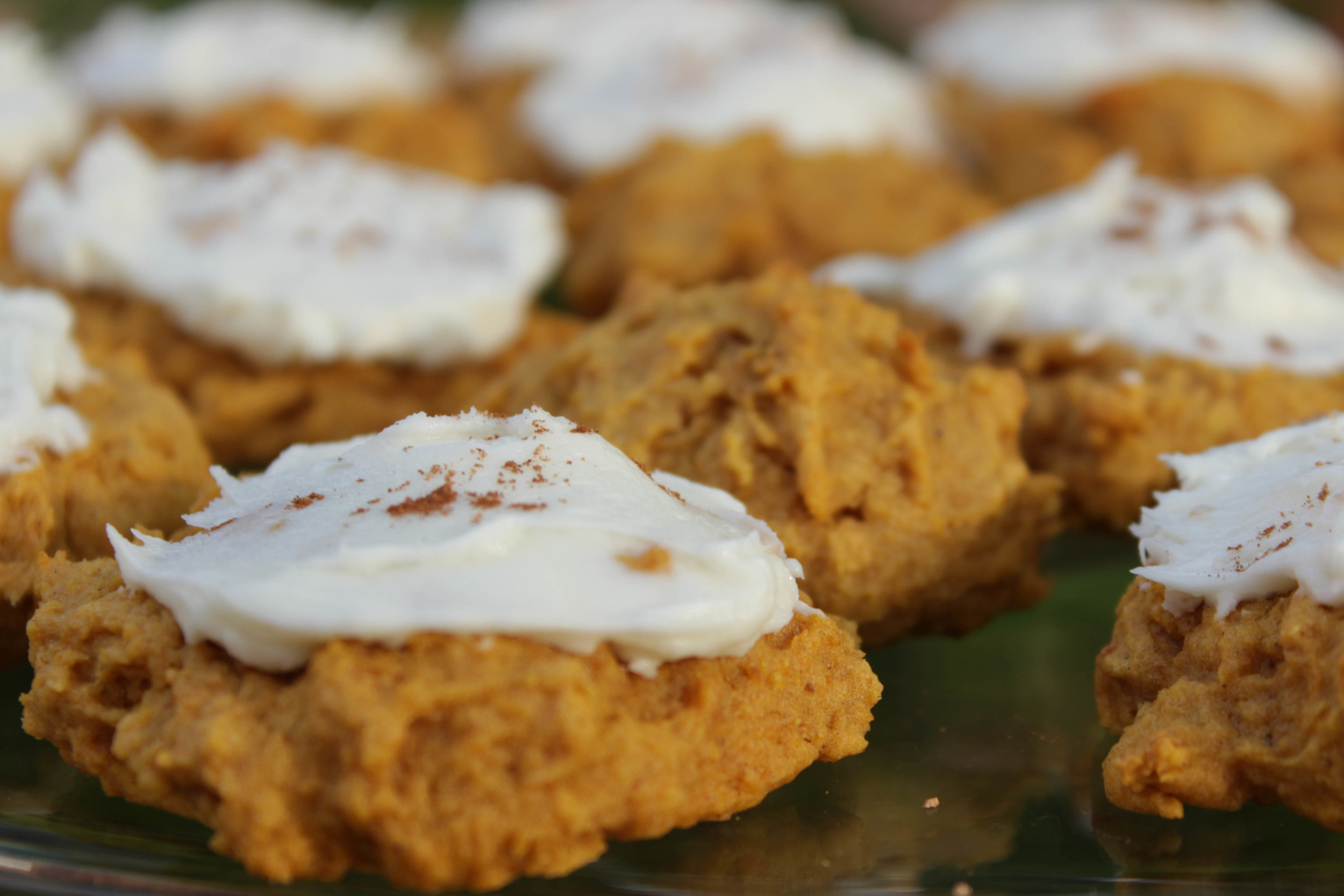 Now, spread a little frosting on each cooled cookie with a spatula. Sprinkle a little cinnamon and/or nutmeg over the top if you like for a little extra flavor.