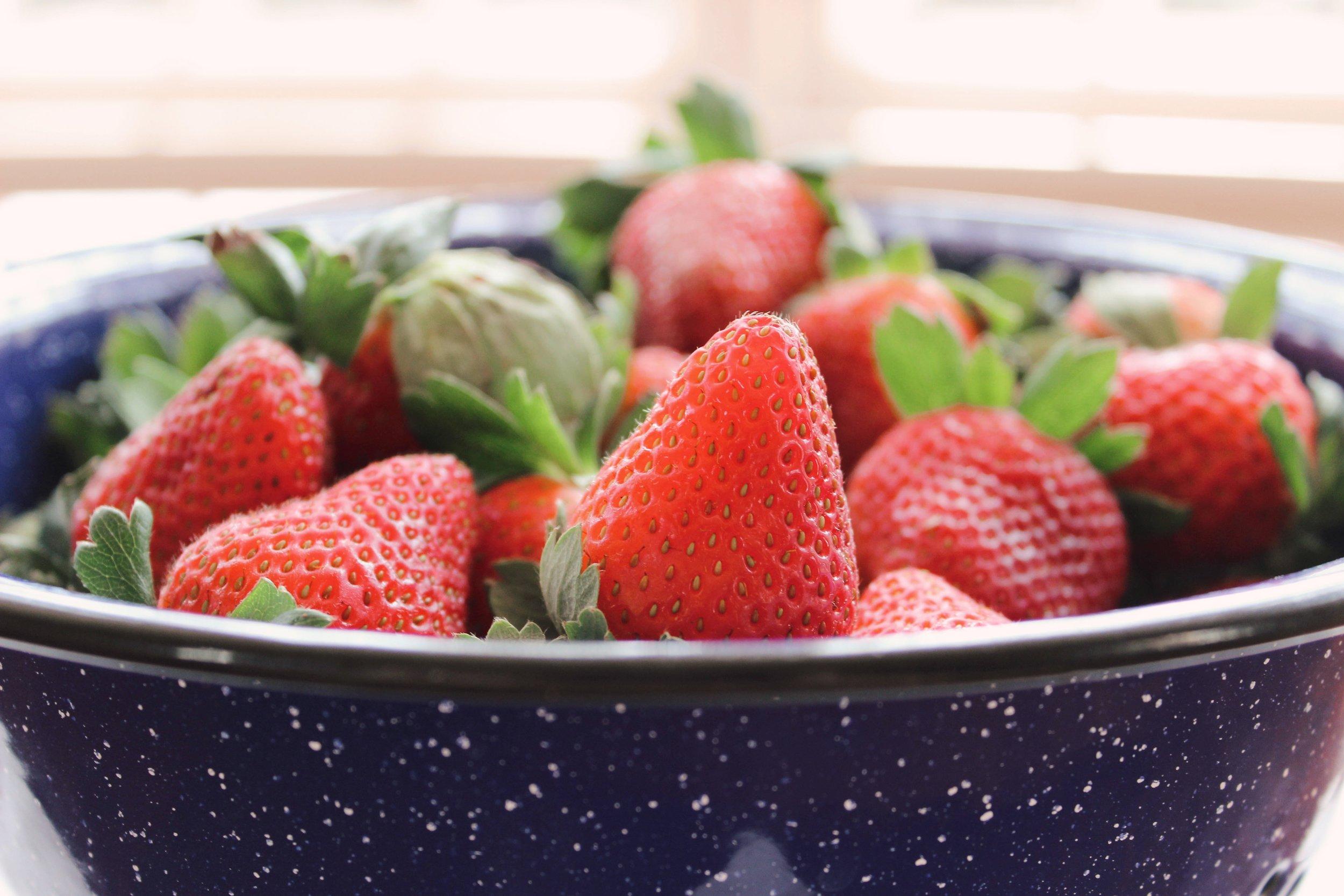 Hull and slice fresh strawberries.
