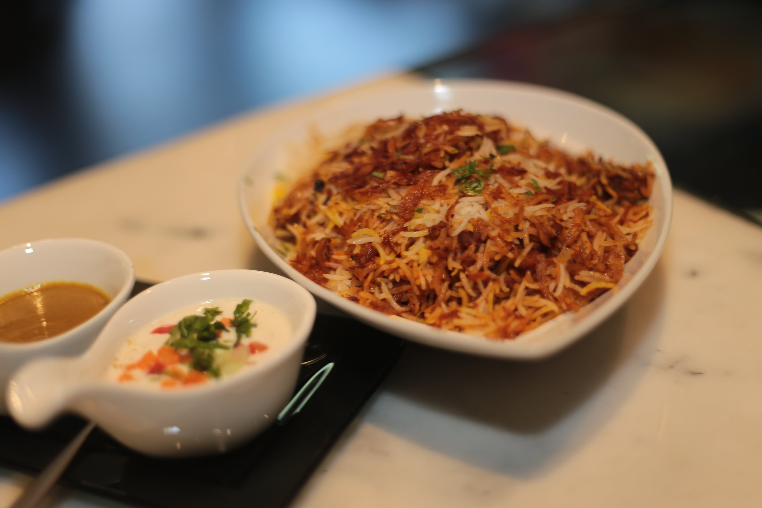 Kache Gosht ki biryani served with Baingan Salan and raita