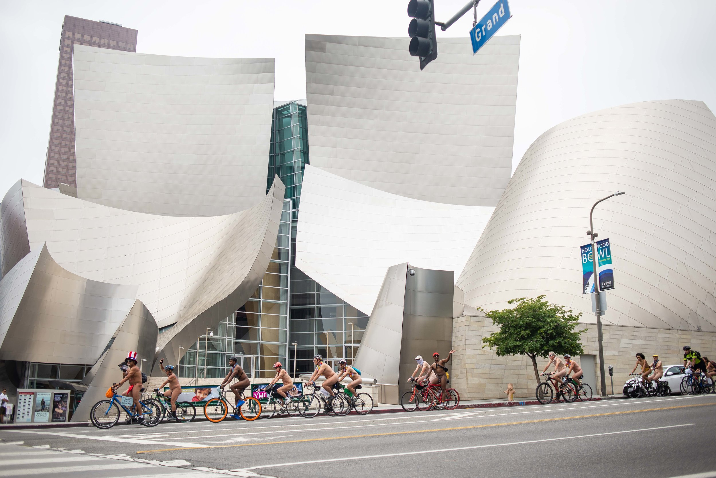 Participants of the World Naked Bike Ride pass the Walt Disney Concert Hall in downtown Los Angeles, Calif. on June 23, 2018.