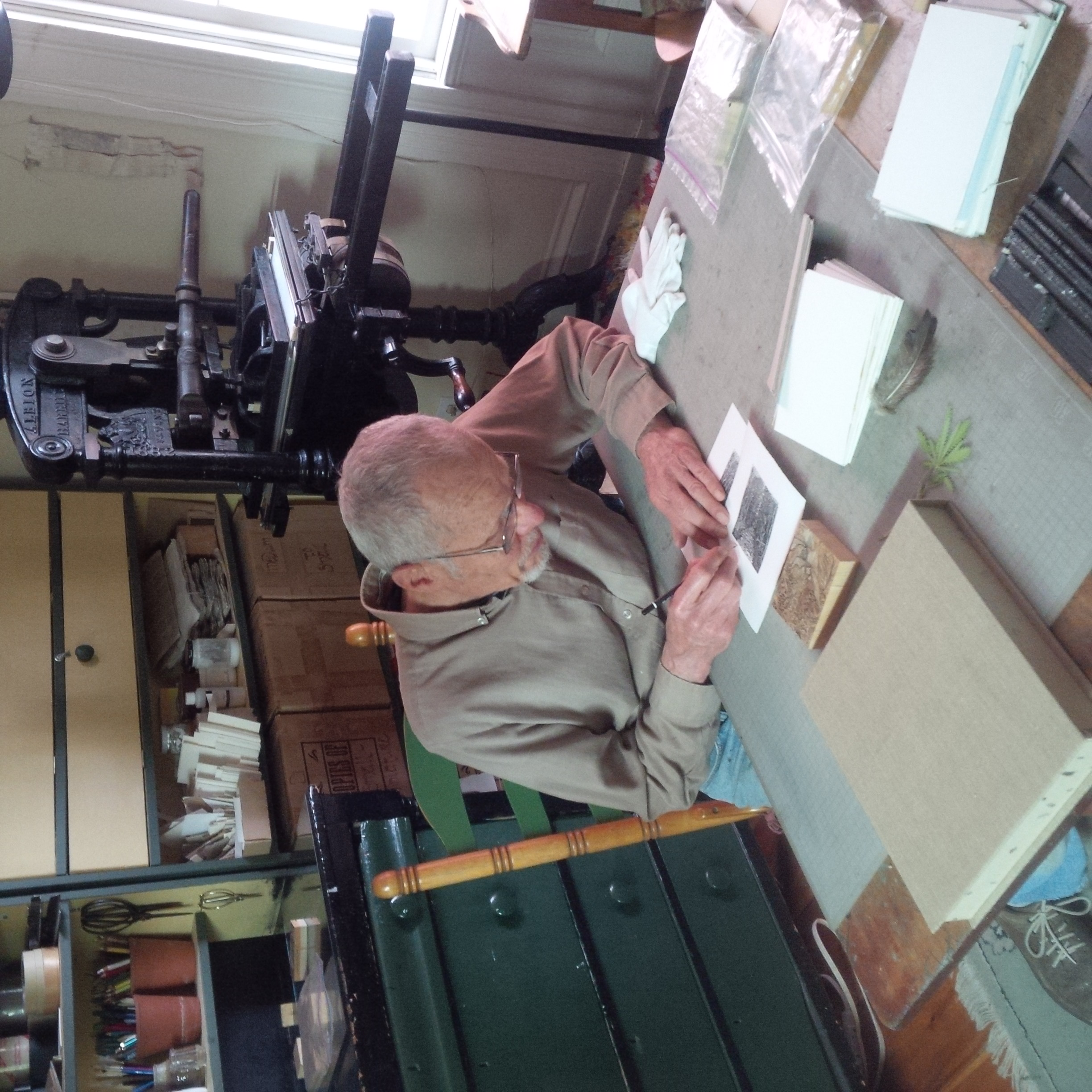 "Gerard signing the first print of ""Walking Home"" at his work table in his heritage home and gallery.  His 1882 printing press is behind him."