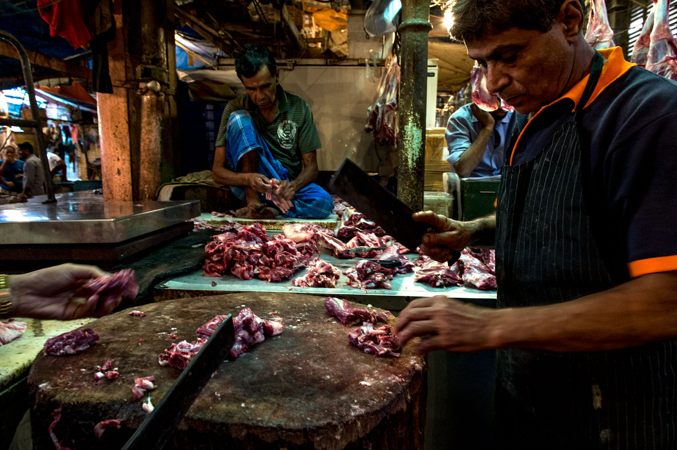 New Market Kolkata India slaughterhouse | Restaurant owner and chef, separating meat from the bone.