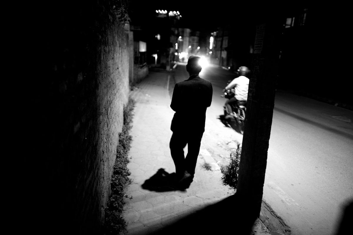 A man is walking under a streetlamp in Boudha, Kathmandu, Nepal.