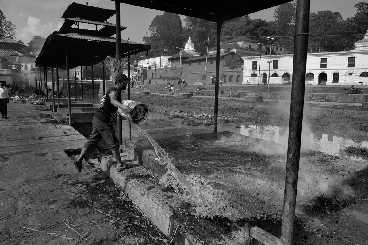 "Antyeṣṭi, ""last sacrifice""  Pashupatinat, on the banks of the Bagmati River. An assistant rinses the Shmashana from the last remains after a cremation. A shmashāna is a Hindu cremation ground, where dead bodies are burnt on a pyre."