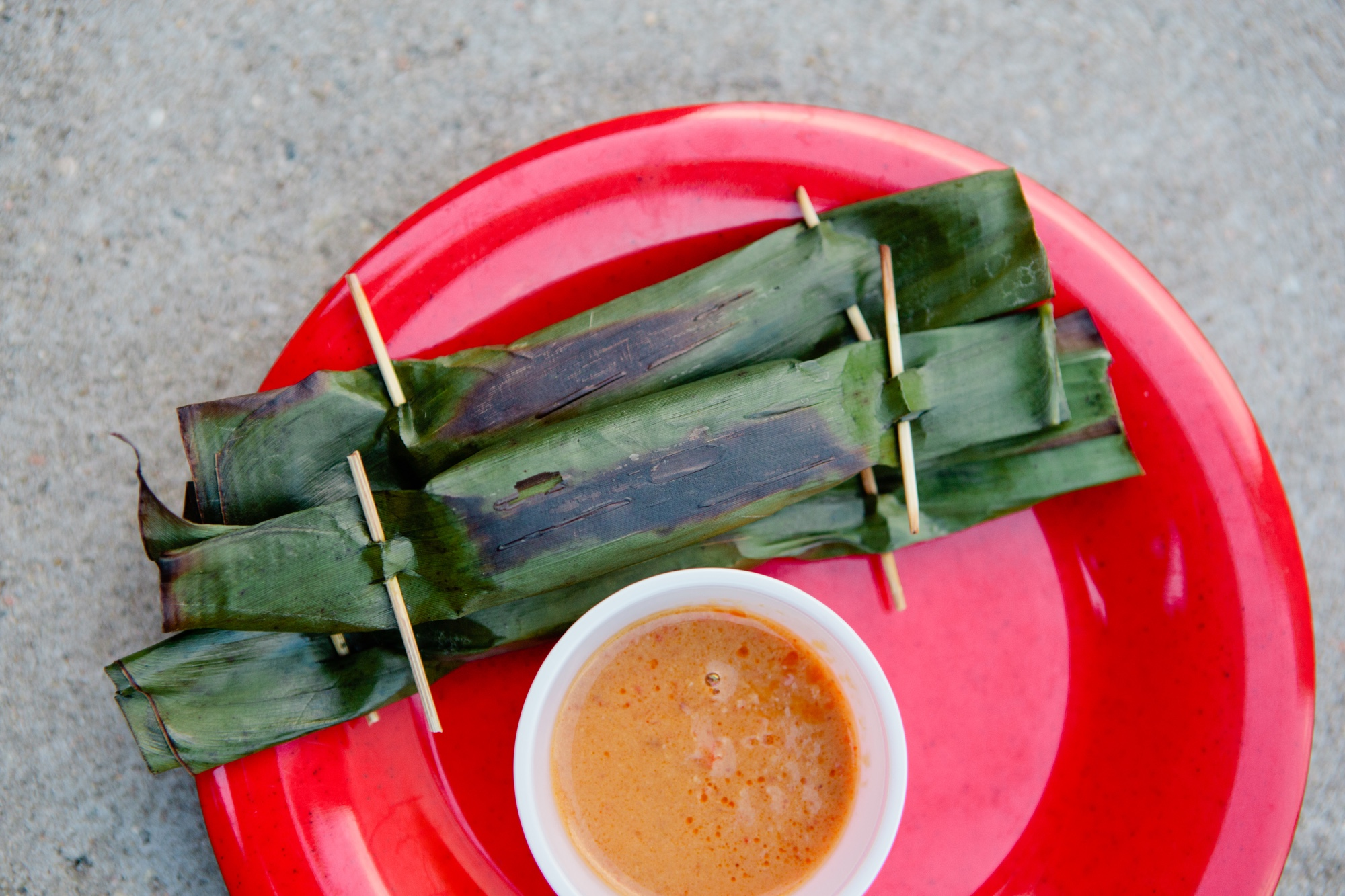 On the menu is Otak-Otak: Grilled fish dumpling wrapped in banana leaf and served with a spicy peanut sauce.