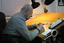 Joe Giella sitting at his drawing board.